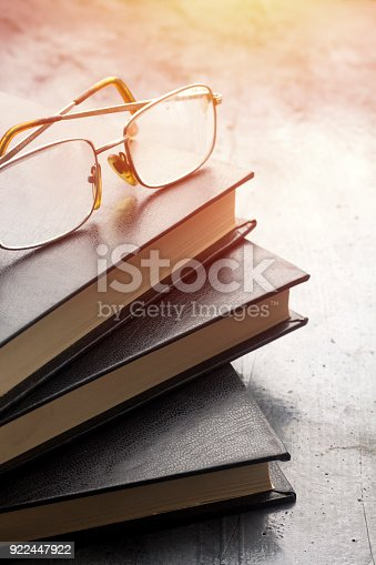 istock stack of books with a pair of eyeglasses on top with sun effect 922447922