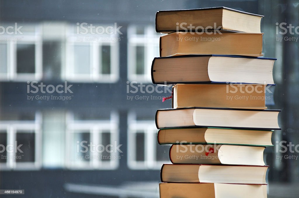 Stack of books with blurred building in background stock photo