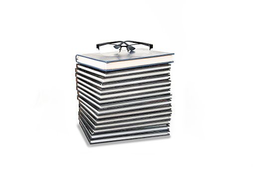 Stack of books with eyeglasses on the white background