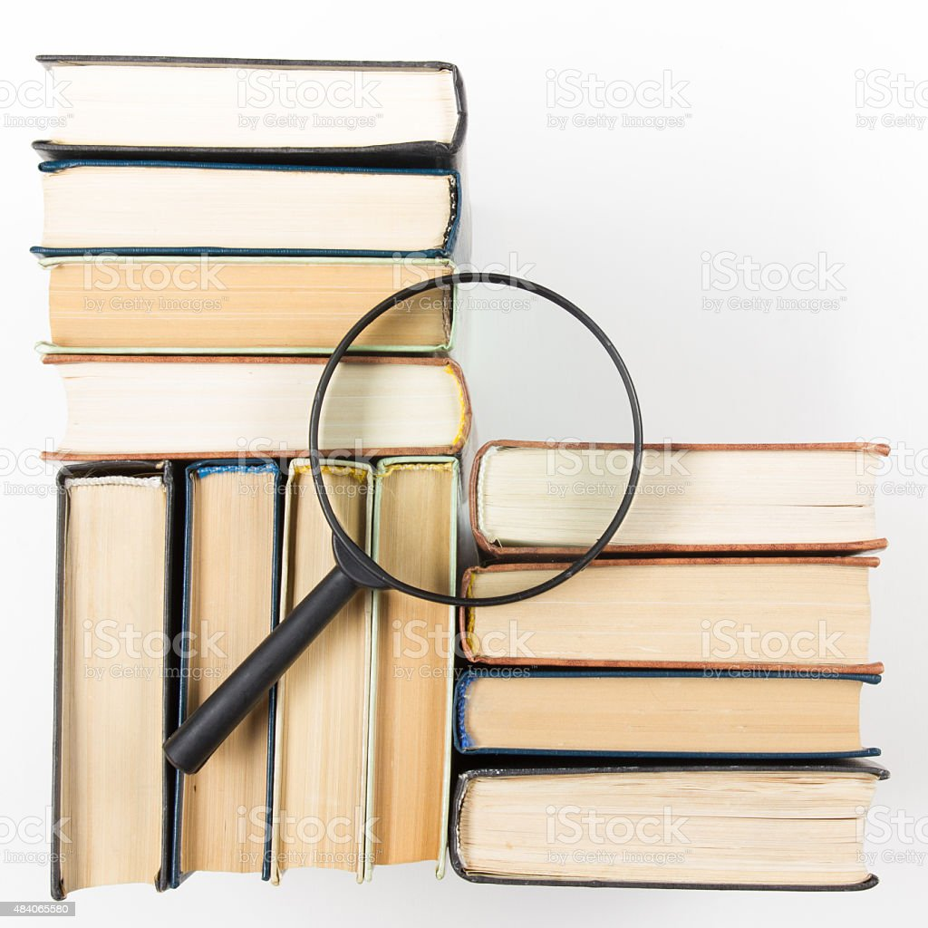 Stack of books with magnifying glass. Search information. stock photo