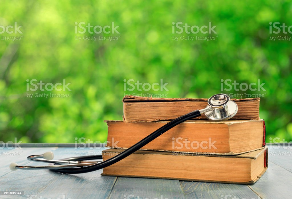 Stack of books with stethoscope on wooden table against the background blur green leaves bokeh stock photo