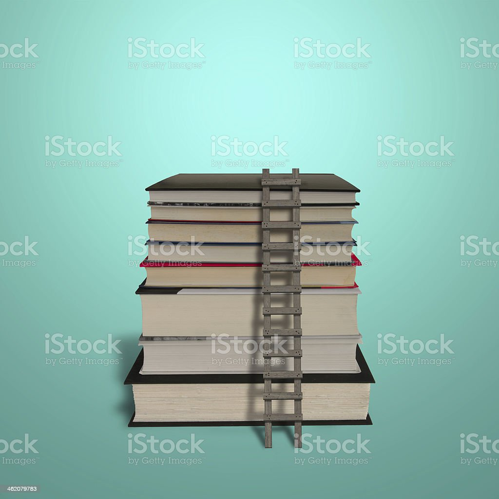 Stack of books with wooden ladder isolated in green royalty-free stock photo