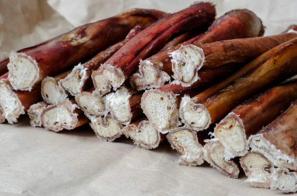 Stack of bully pizzle for dogs close-up. Stack of bully pizzle for dogs close-up. Group of dental bully sticks on brown paper. The process of packaging chewing treats for pets. Pet shop, pet supplies creative background. Copy Space animals with big penis stock pictures, royalty-free photos & images
