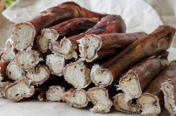 Stack of bully pizzle for dogs close-up Stack of bully pizzle for dogs close-up. Group of dental bully sticks on brown paper.  Pet shop, pet supplies creative background. animals with big penis stock pictures, royalty-free photos & images