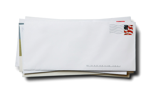 A stack of blank business envelopes with a cancelled U.S. flag stamp isolated on a white background with a soft shadow.