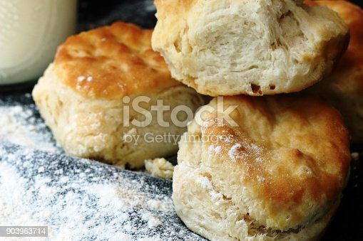 Stack of three buttermilk handmade biscuits from scratch with flour