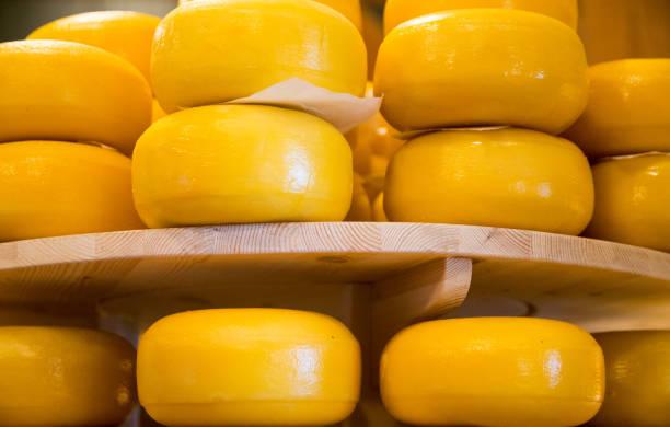 stapel von käse in einem geschäft in amsterdam, niederlande - wie alt werden kühe stock-fotos und bilder