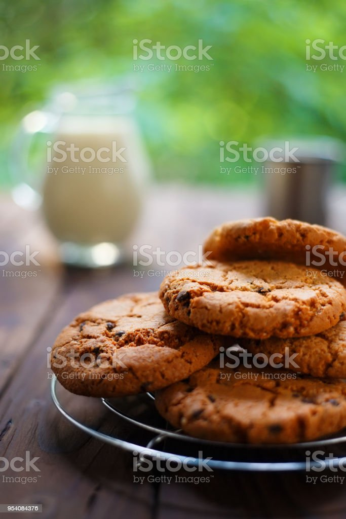 Stack of chocolate chip cookie and glass jug of milk on rustic w stock photo