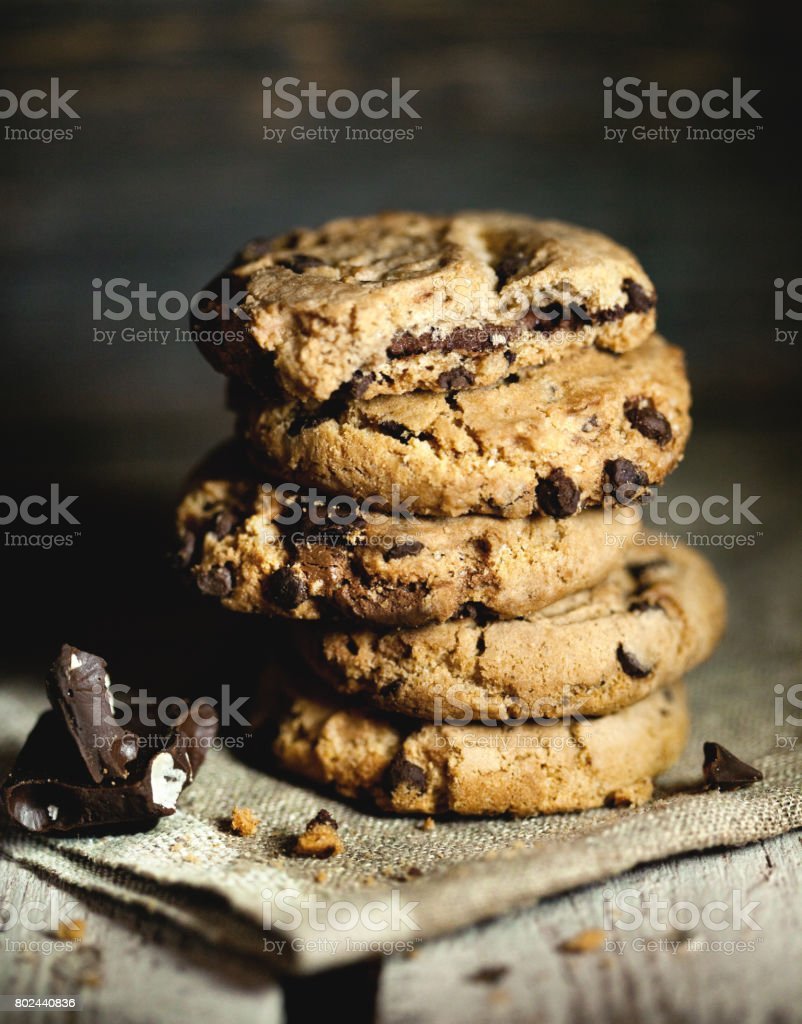 Stack of chocolate chip cookies and chocolate on wooden table. stock photo