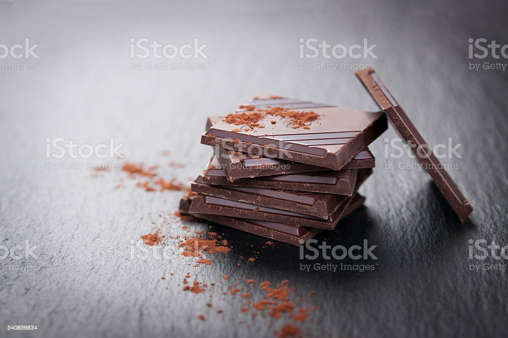 Stack of chocolate chunks on a dark stone background stock photo