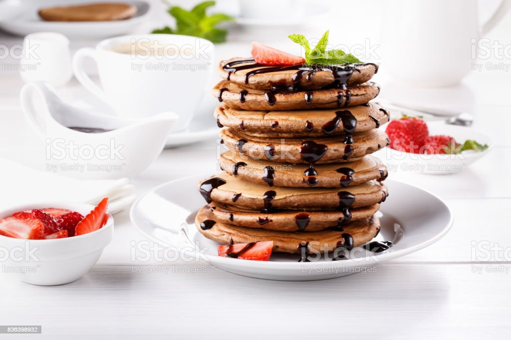 Stack of chocolate pancakes with chocolate topping and strawberries