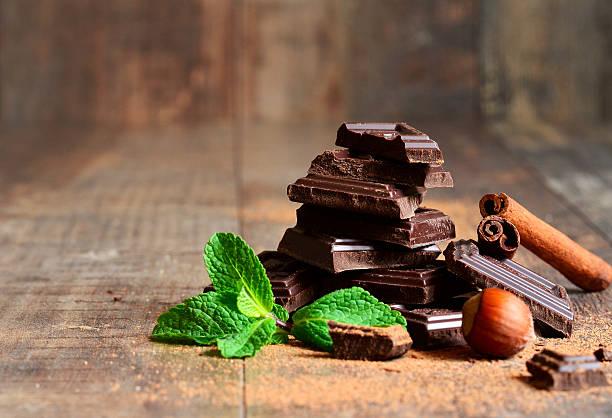 stack of chocolate slices with mint leaf,hazelnut and cinnamon. - nane şeker stok fotoğraflar ve resimler