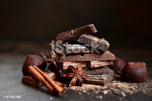 Stack of chocolate slices with spices on a dark slate, stone or concrete background.