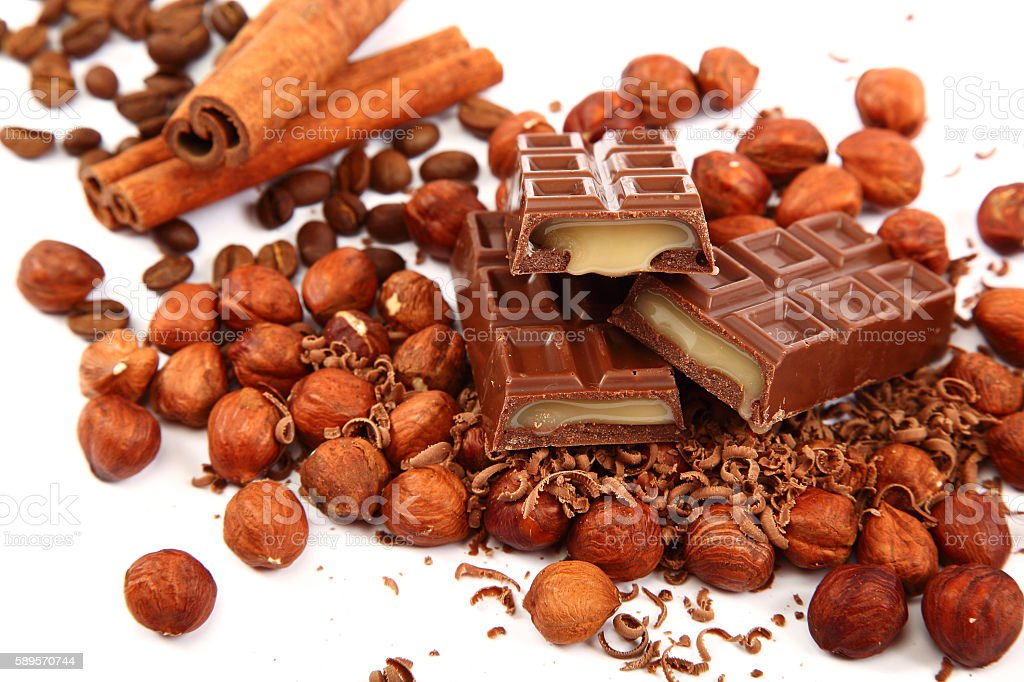 Stack of chocolate tiles with hazelnuts and cinnamon sticks. stock photo