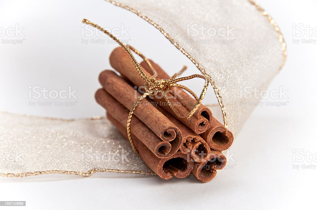 Stack of cinnamon sticks decorated with gold ribbons stock photo