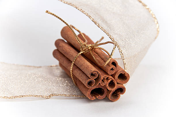 Stack of cinnamon sticks decorated with gold ribbons