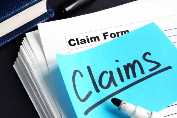 Stack of Claims applications on a desk. stock photo