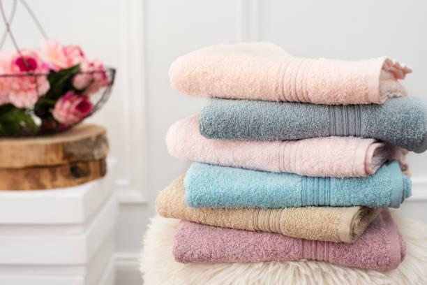 stack of clean soft colorful towels. flowers on background - стирка стоковые фото и изображения
