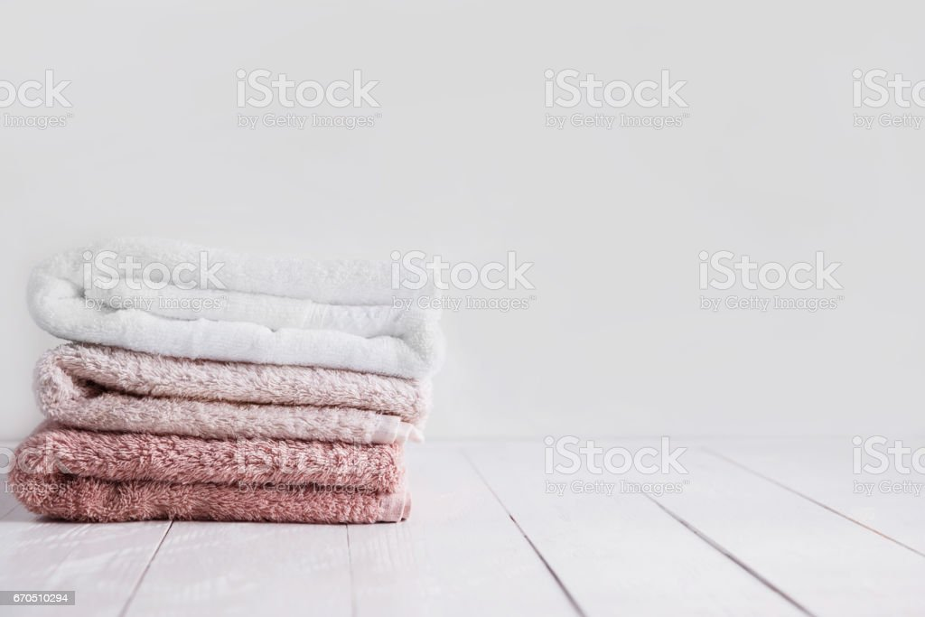 Stack of clean towels on wooden table in bathroom. stock photo