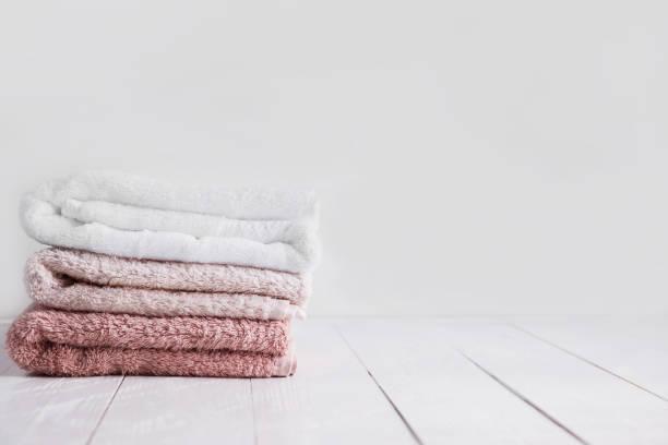 stapel von saubere handtücher auf holztisch im badezimmer. - stoffregal stock-fotos und bilder