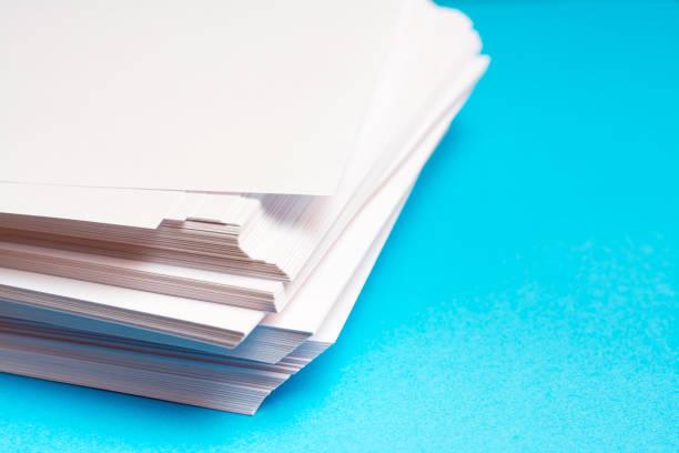 Mavi arka plan üzerindeki bir masanın üzerinde temiz beyaz kağıt yığını stok fotoğrafı