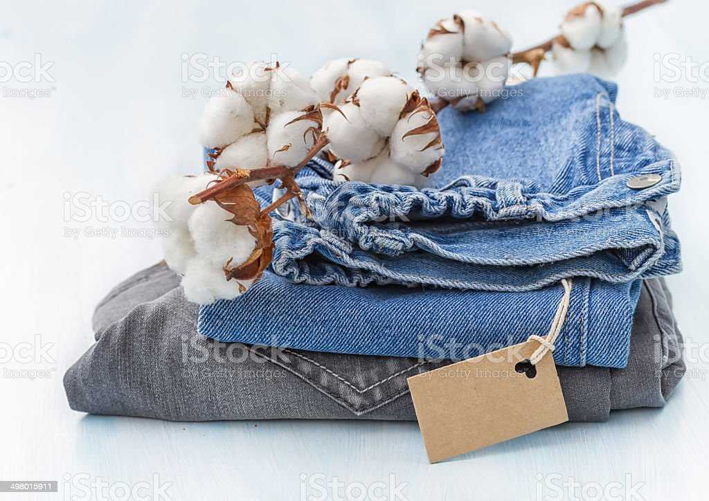 Stack of clothes with a sprig of cotton stock photo