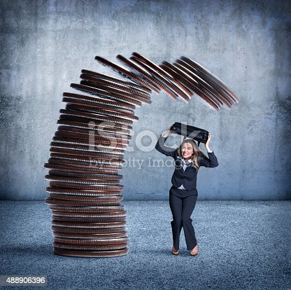 A stack of coins teeters as it is about to fall onto a businesswoman who is using her shoulder bag as protection. She is bending at the knees and wincing in anticipation of the impending collapse.