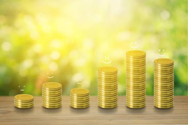 Stapel von Münzen, Financial, Business sparen und Zinsen erhöhen Konzept auf Teakholz. Emotion Lächeln traurig glücklich auf dem Stapel der Münze. Natürliches Grün und Bokeh mit Sonnenlicht Hintergrund. – Foto