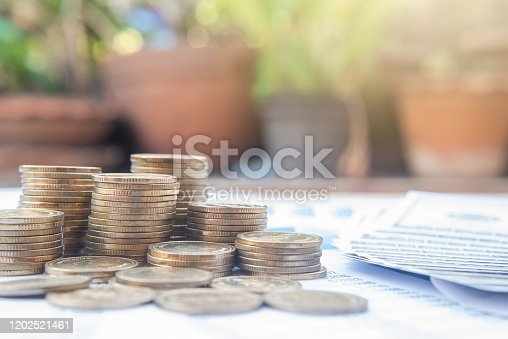 467271788 istock photo Stack of coins on blue pastel chart paper and blur nature background with sun light. Business, finance, marketing, e-commerce concept and design. 1202521461