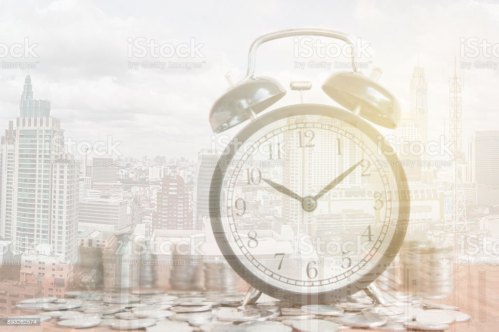 Stack of coins with black fashioned alarm clock for display planning money financial and business accounting concept, time is money concept with clock and coins, time to work at make money, Double exposure stock photo