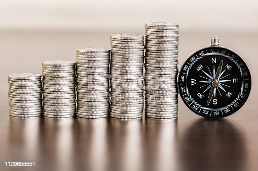 istock Stack of coins with compass on wood table 1129655551