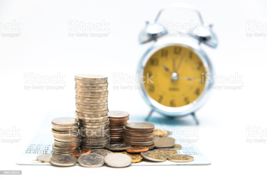 Stack of coins with vintage clock on white background for mocup display planning Money Financial and business Accounting Concept stock photo