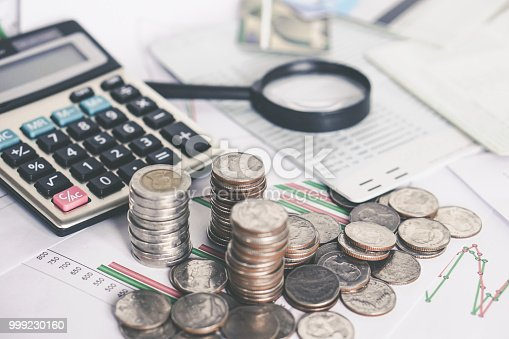 istock stack of coins,calculator,saving account on desk 999230160