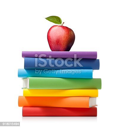 Stack of colored books with apple on white background.