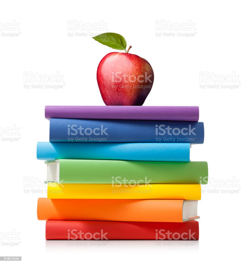 Stack of colored books with apple on white background stock photo