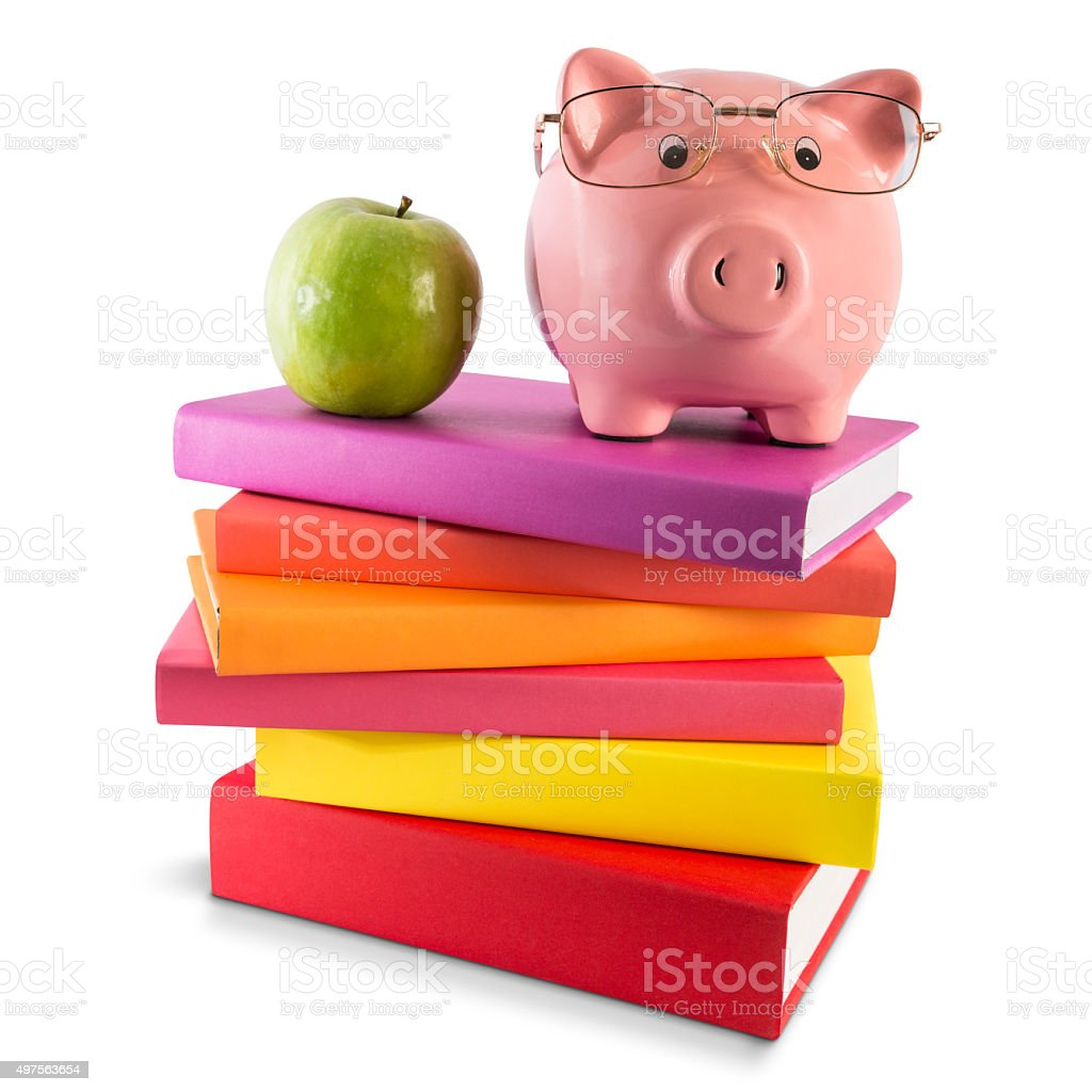 Stack of colored books with piggy bank and green apple stock photo