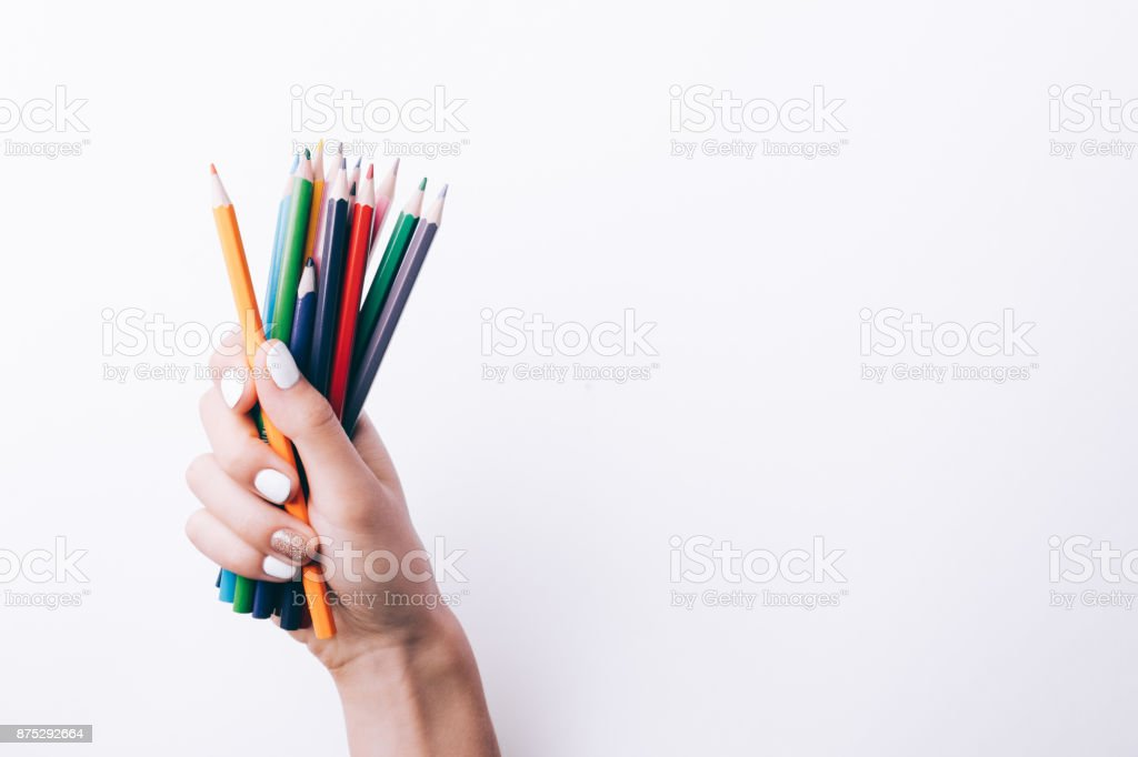 Stack of colored pencils in a female hand stock photo