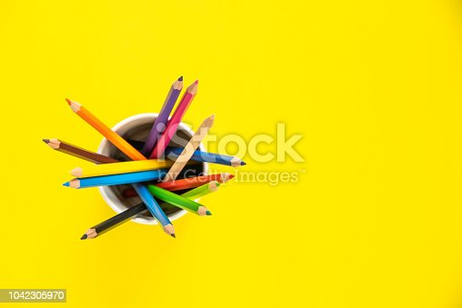951081060 istock photo Stack of colored pencils in a glass on yellow background 1042305970