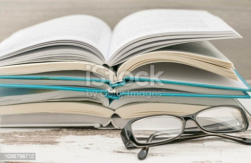 istock Stack of colorful books and glasses . Education background. Back to school. Book, hardback colorful books on wooden table. Education business concept. Copy space for text 1056796712