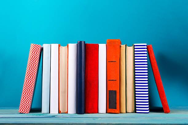 Pila de coloridas sucia de libros, fondo azul de cortesía, espacio de copia - foto de stock