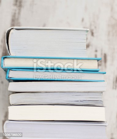 508711370 istock photo Stack of colorful books, grungy  wooden background, free copy space 1056796520