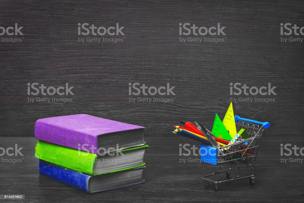Stack of colorful books on a wooden table, and grocery cart with school stationery. Back to school. stock photo