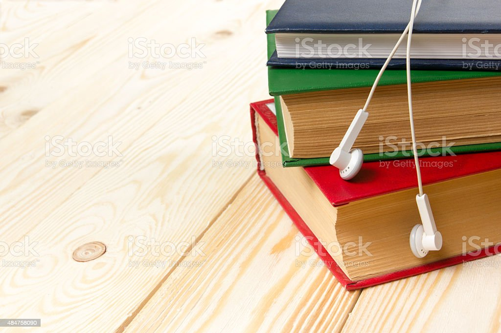 Stack of colorful books on wooden table and headphones. stock photo
