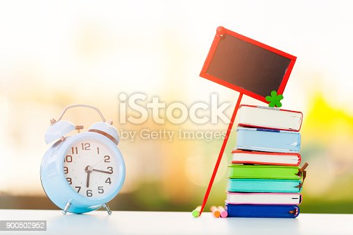 Stack of colorful books with blue clock