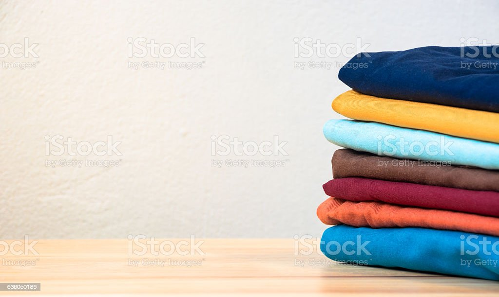 Stack of colorful clothes on wood table stock photo