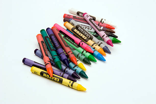 A stack of colorful crayons on a white background stock photo
