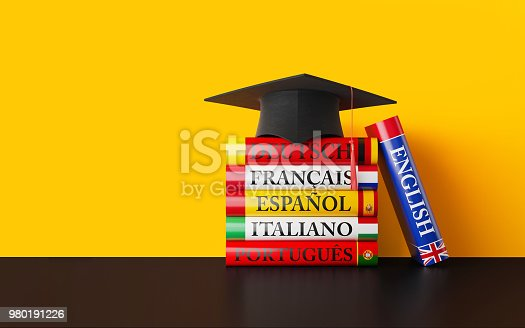 Stack of colorful dictionaries with a blackboard and a graduation cap in front of a yellow wall background. English, German, Portuguese, Spanish, French and Italian dictionaries are sitting on top of each other. Isolated on white background. Horizontal composition with copy space.