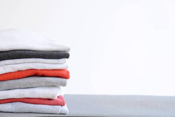 stapel von bunten gefaltete hemden auf grauen tabelle - kleidung falten stock-fotos und bilder