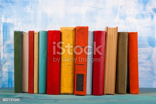 istock Stack of colorful hardback books, open book on blue background 502131042