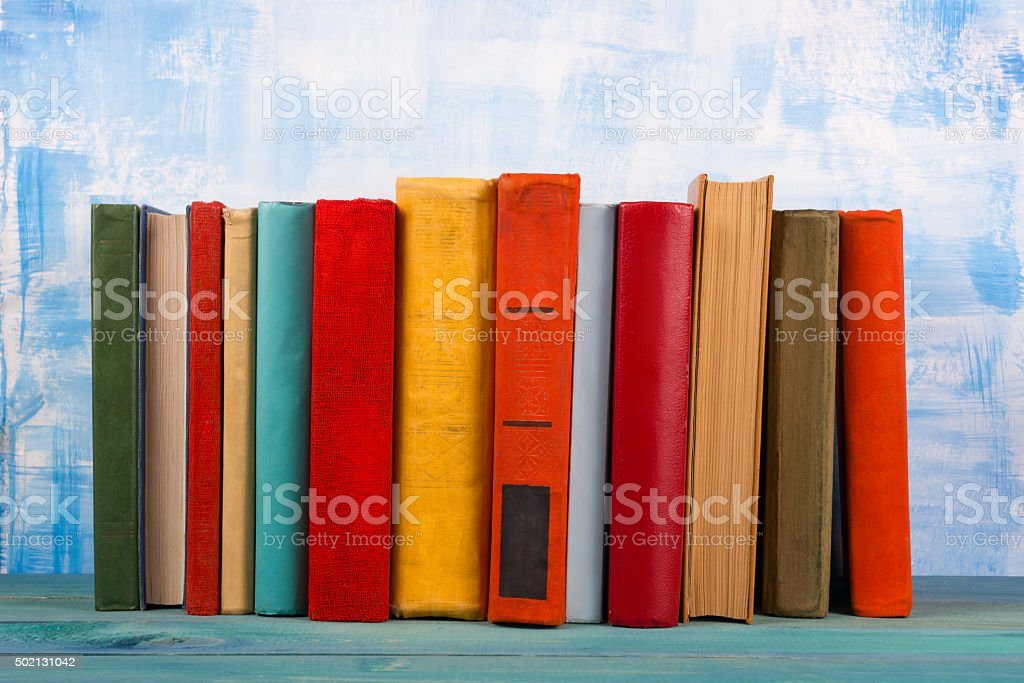 Stack of colorful hardback books, open book on blue background stock photo